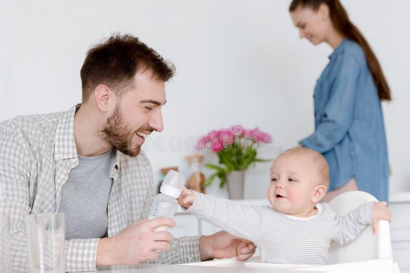 niño de alimentación sonriente del padre con leche en la situación de la madre del biberón imagenes de archivo