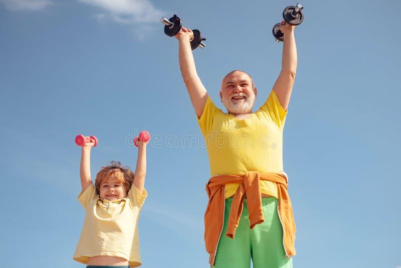 Niño de ayuda de abuelo que ejercita con pesas de gimnasia Hombre mayor y niño en club de salud de la familia Localizaci?n del pa fotografía de archivo