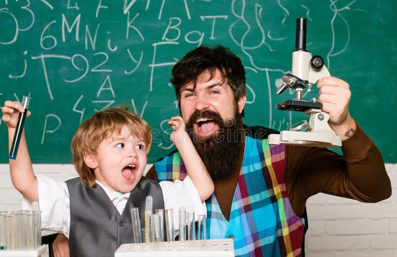 Niño de ayuda del profesor con su preparación en sala de clase en la escuela Ni?o y profesor en el cuarto de clase Peque?o feliz fotos de archivo libres de regalías