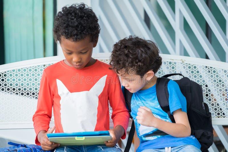 Niño de dos muchachos que se sienta en banco y que juega al juego en la tableta en el preschoo, concepto de la educación escolar  fotos de archivo