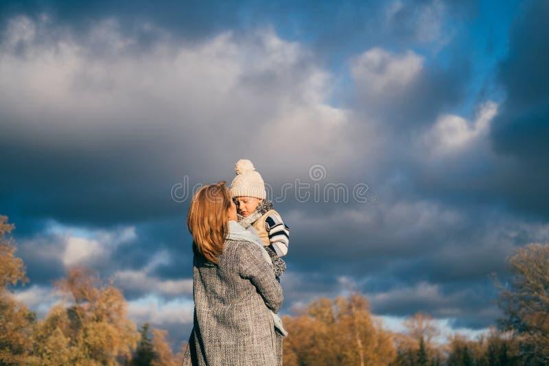 Niño de elevación de la madre en aire en parque del otoño en puesta del sol La familia que se divierte, abrazando, risa, relajánd fotografía de archivo