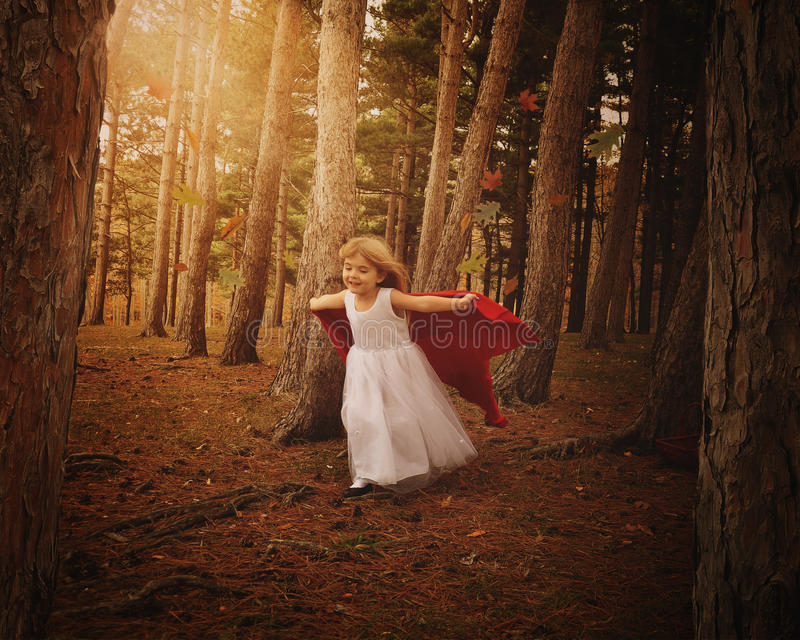 Niño de la aventura que corre en bosque con las hojas de la caída imagen de archivo