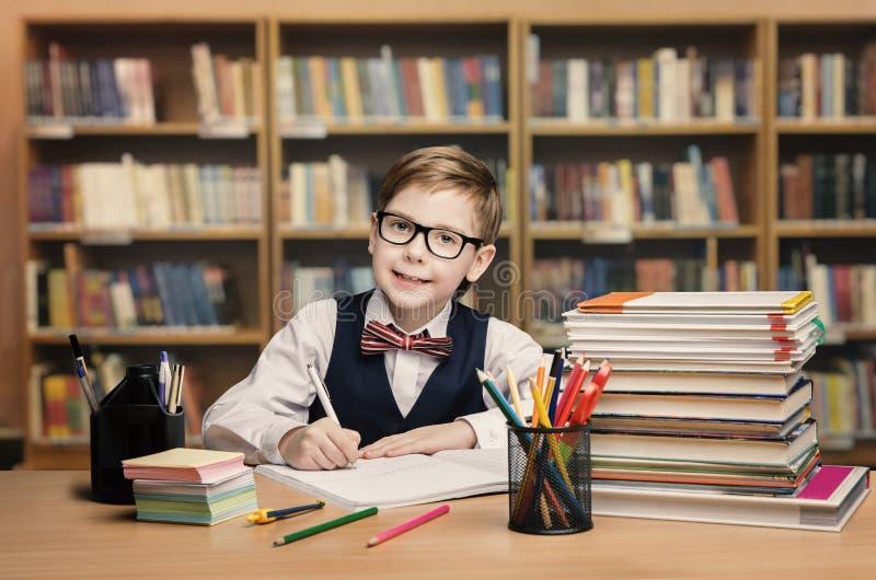 Niño de la escuela que estudia en la biblioteca, libro de la escritura del niño, estantes imagen de archivo