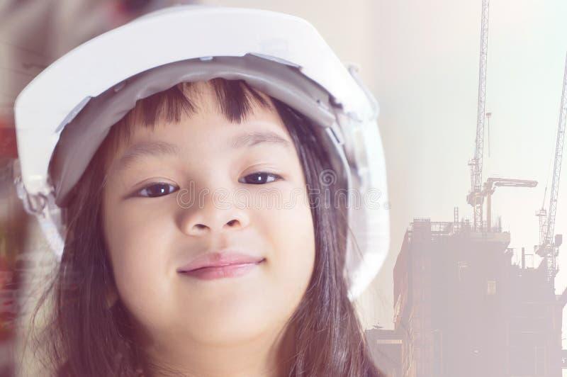 Niño de la ingeniería con el sombrero de seguridad en fondo de la construcción imagenes de archivo
