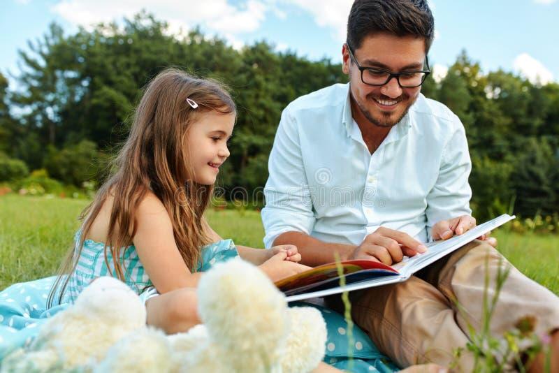 Niño de la lectura del papá un libro en parque Padre e hija en naturaleza imagenes de archivo
