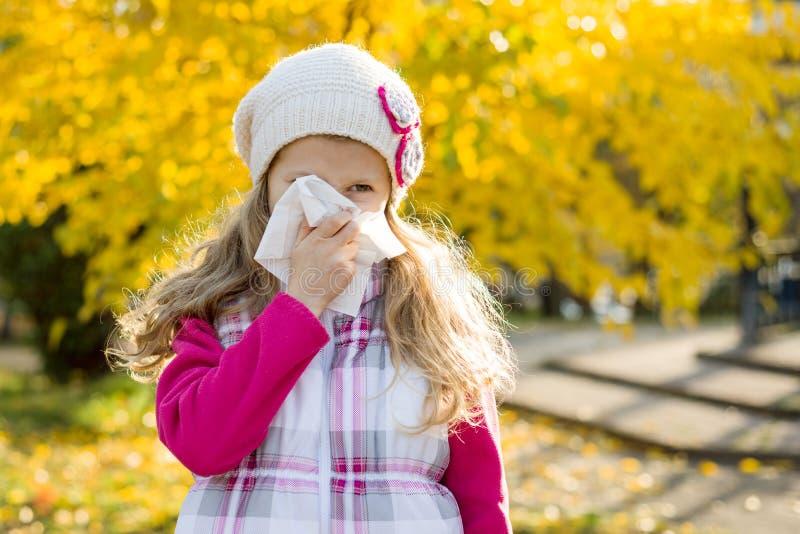 Niño de la muchacha con rinitis fría en el fondo del otoño, temporada de gripe, mocos de la alergia imagen de archivo libre de regalías