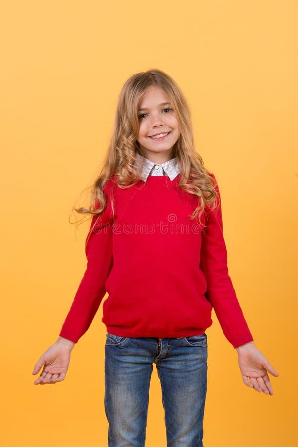 Niño de la muchacha con sonrisa en suéter y tejanos rojos fotos de archivo