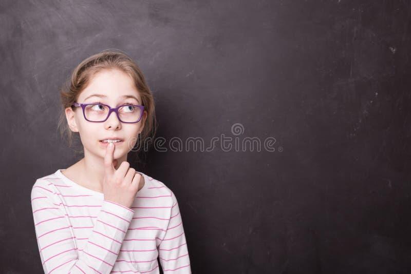 Niño de la muchacha del alumno, alumno que piensa en la pizarra foto de archivo