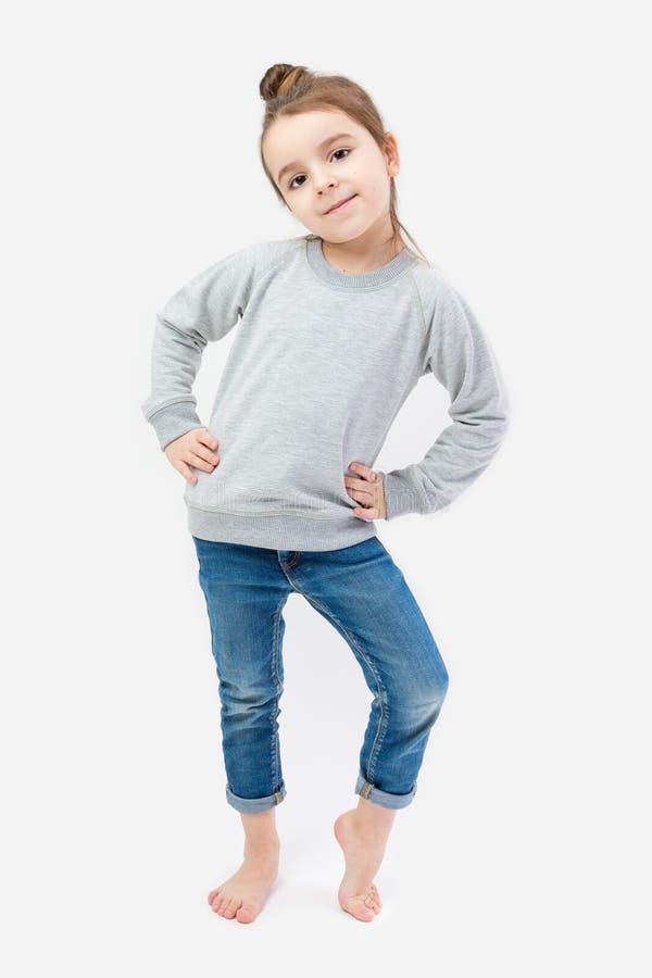 Niño de la muchacha descalzo en vaqueros y un jersey gris imagen de archivo libre de regalías