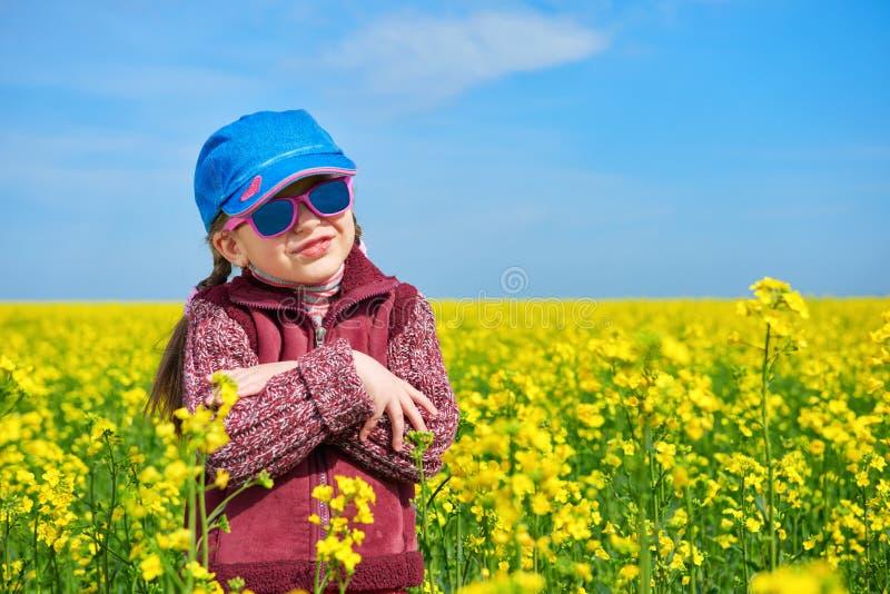 Niño de la muchacha en el campo con las flores amarillas brillantes, paisaje de la rabina de la primavera imagen de archivo libre de regalías