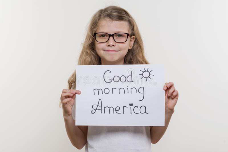 Niño de la muchacha que lleva a cabo el trozo de papel con la palabra GOOD MORNING AMERICA Bakgrounde blanco fotografía de archivo