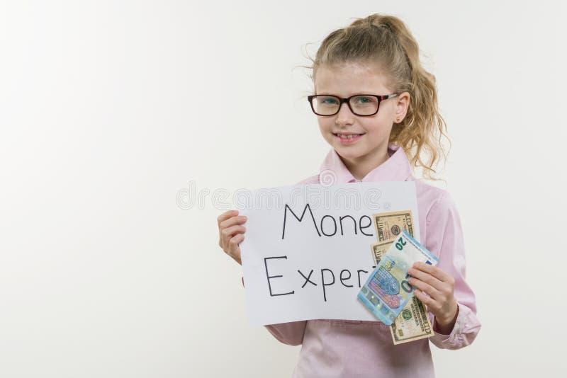 Niño de la muchacha que lleva a cabo el trozo de papel con un EXPERTO de la palabra DINERO Bakgrounde blanco, espacio de la copia imagen de archivo
