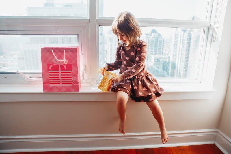 Niño de la muchacha que se sienta en el travesaño de la ventana en casa que abre los regalos de cumpleaños fotos de archivo libres de regalías