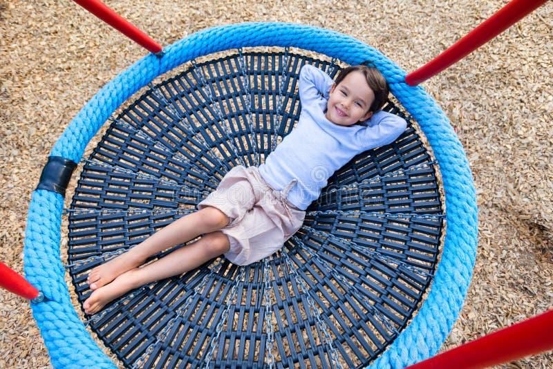 Niño de la muchacha que se sienta en un oscilación en el patio del jardín imagen de archivo libre de regalías