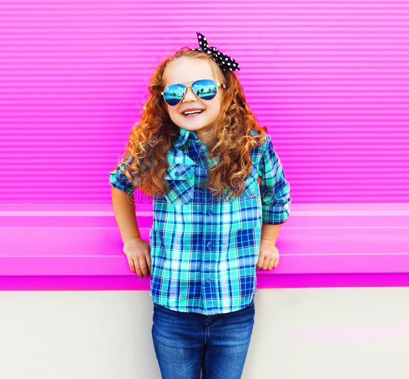 Niño de la niña del retrato en la camisa a cuadros, gafas de sol en la pared rosada colorida imágenes de archivo libres de regalías