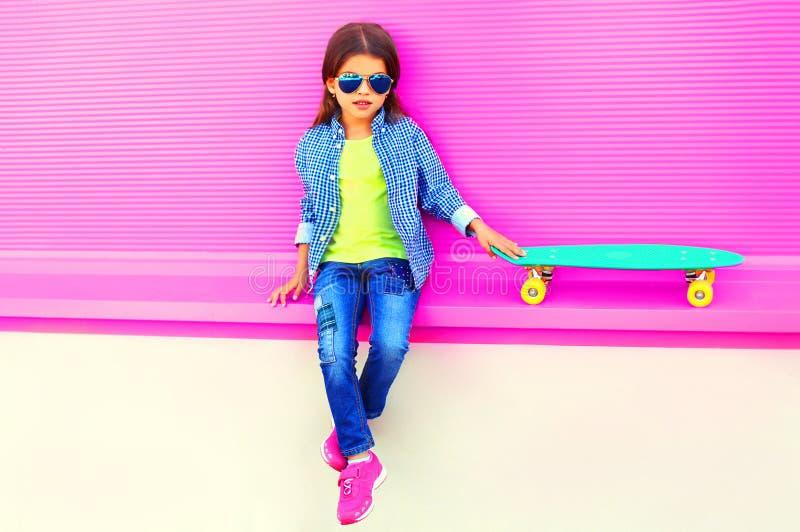 Niño de la niña de la moda que se sienta con el monopatín en ciudad en la pared rosada colorida imágenes de archivo libres de regalías
