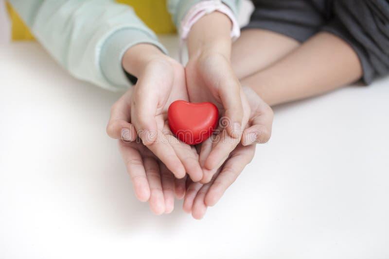 Niño de la remolque que lleva a cabo el corazón rojo, primer Concepto de la adopción fotografía de archivo