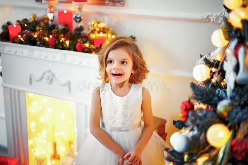 Niño de Laughinhg que mira furtivamente de detrás el árbol de navidad imágenes de archivo libres de regalías