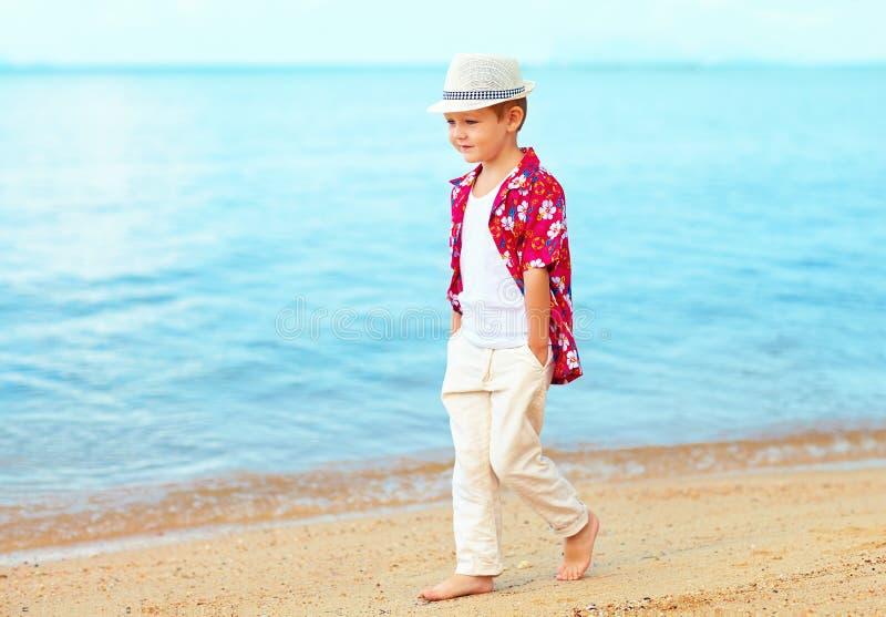 Niño de moda hermoso, muchacho que camina en la playa arenosa imagen de archivo
