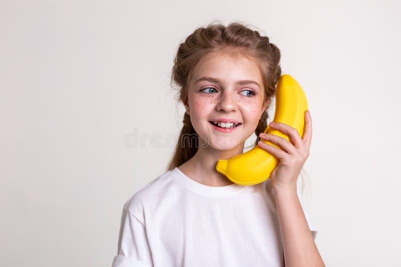 Niño de pelo largo alegre con los ojos azules que llevan el plátano plástico fotos de archivo libres de regalías