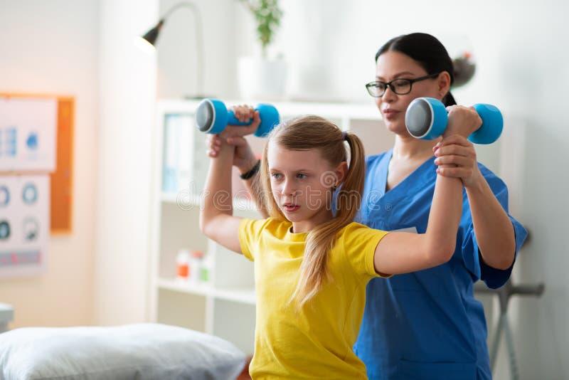Niño de pelo largo atento que lleva pesas de gimnasia pesadas con la ayuda del doctor fotos de archivo libres de regalías
