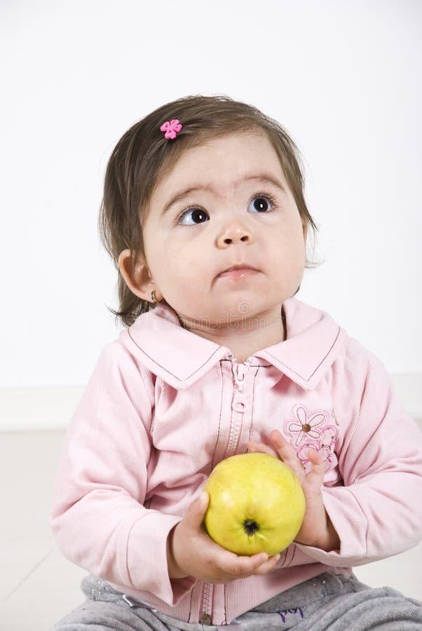 Niño de pensamiento con una manzana foto de archivo libre de regalías