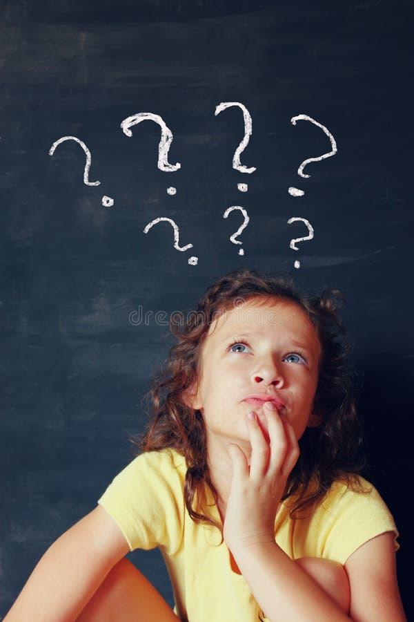 Niño de Qute al lado del thinking del chalkbord con muchos símbolos de los signos de interrogación fotos de archivo