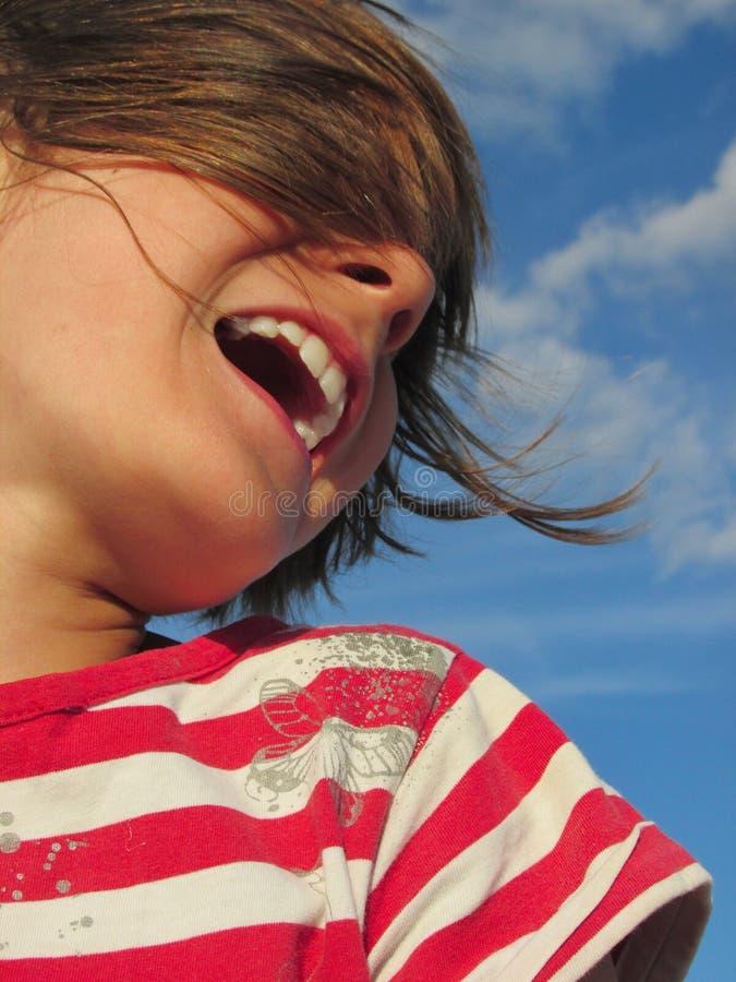 Niño de risa feliz contra el cielo azul imagen de archivo
