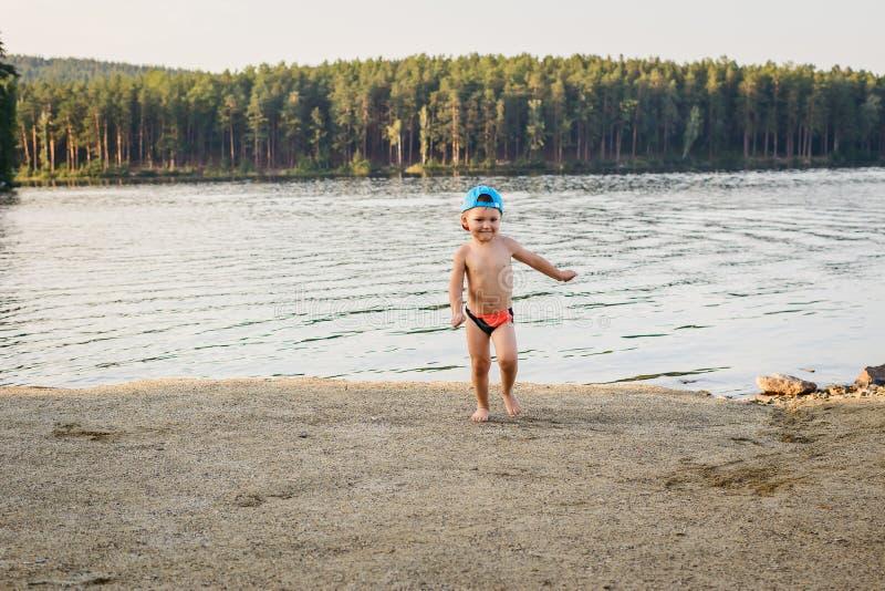 Niño de tres años que corre en el lago fotografía de archivo