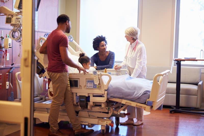 Niño de Visiting Parents And del pediatra en cama de hospital fotos de archivo