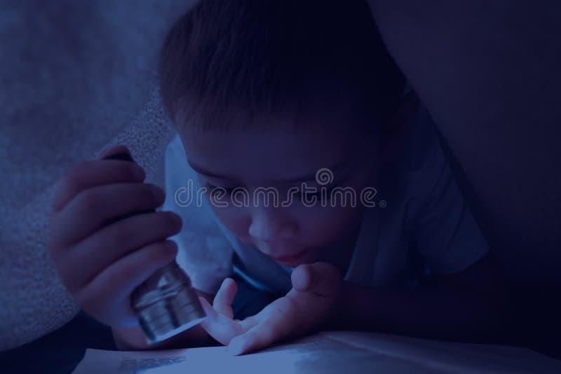 Niño de Yound que lee el libro interesante en la noche con la ayuda de la linterna Aventura y secretos Concepto de leer un intere fotos de archivo