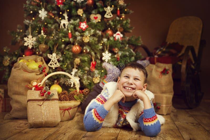 Niño debajo del árbol de Navidad, niño de la Navidad del muchacho de la Feliz Año Nuevo imagen de archivo libre de regalías