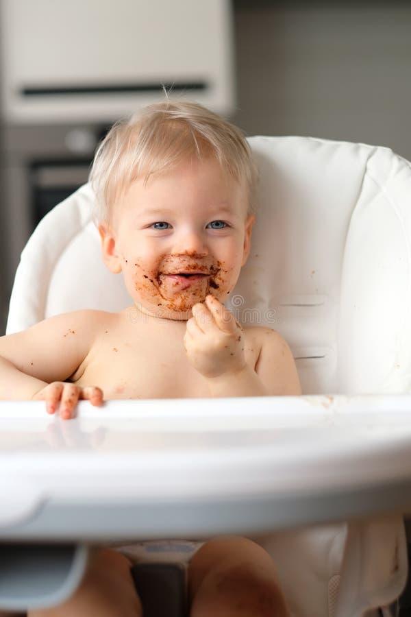 Niño del bebé del niño que come la fruta con la cara sucia sucia imágenes de archivo libres de regalías