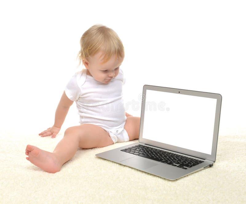 Niño del bebé del niño que se sienta cerca del la inalámbrico moderno del ordenador imagenes de archivo