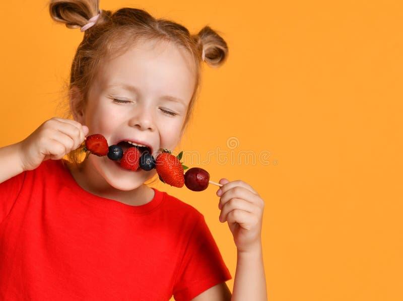 Niño del bebé en la camiseta roja que lleva a cabo oler que muerde comiendo el postre fresco de las bayas con la frambuesa de la  imagen de archivo