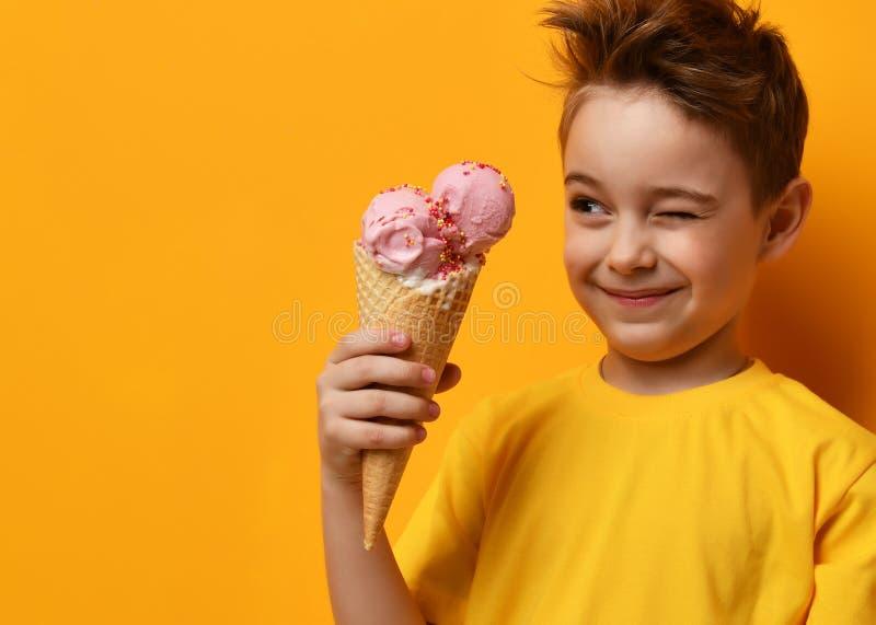 Niño del bebé que come el helado de fresa en cono de las galletas y que guiña en amarillo imagen de archivo