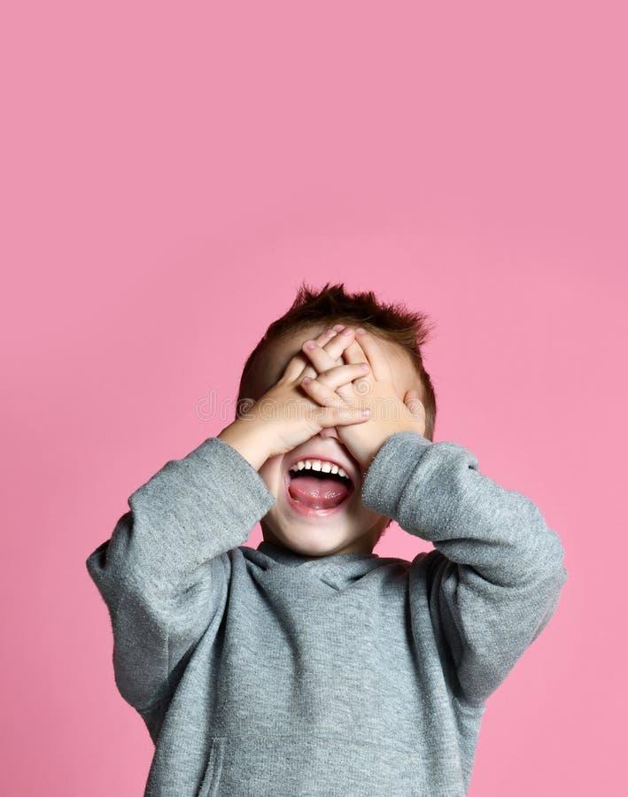 Niño del bebé que cubre cerca sus ojos con las manos y las palmas que gritan la risa sobre rosa fotografía de archivo libre de regalías