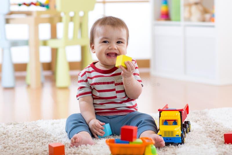 Niño del bebé que ríe y que juega con los juguetes coloridos que se sientan en la alfombra suave en cuarto de niños foto de archivo libre de regalías