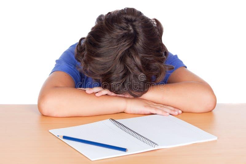 Niño del estudiante dormido en su escritorio imagenes de archivo