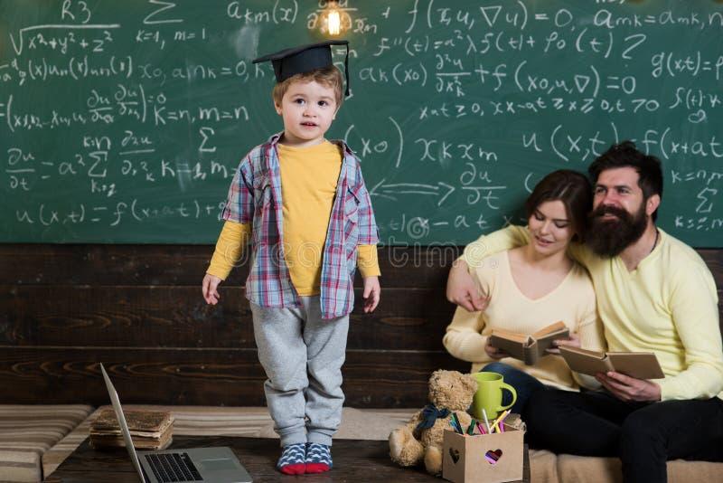 Niño del genio en casquillo de la graduación Pequeño hometask de la respuesta del genio en sala de clase Familia orgullosa de hij imagenes de archivo