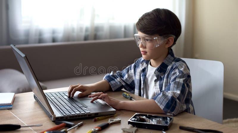 Niño del genio en las gafas de seguridad que buscan instrucciones en línea a los detalles de la PC imagen de archivo libre de regalías