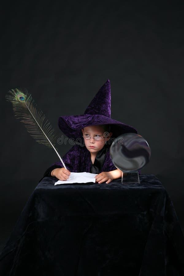 Niño del mago con la pluma de la pluma del pavo real imagen de archivo libre de regalías