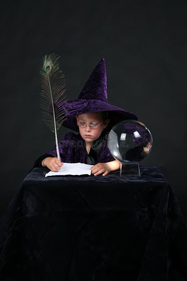 Niño del mago que escribe un encanto imagenes de archivo