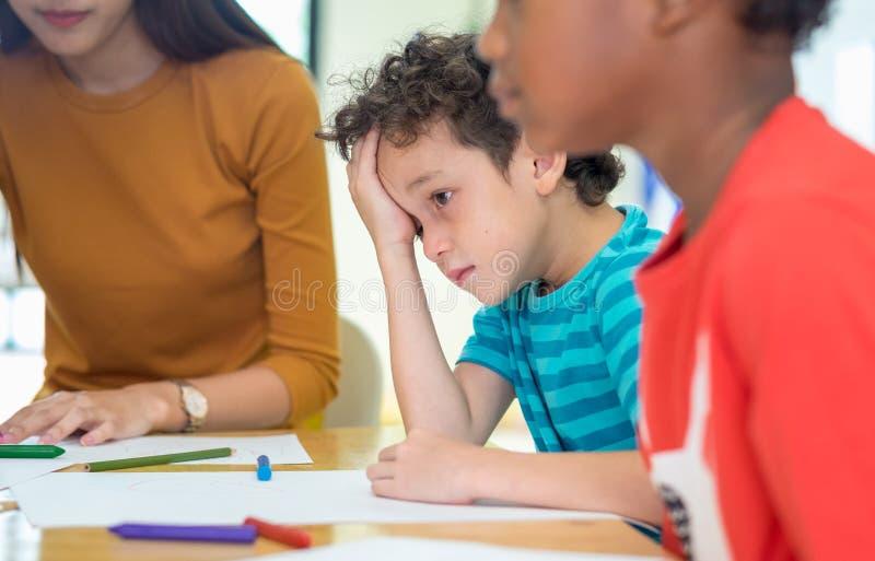 Niño del muchacho de Caucasion con la emoción de la tristeza que se sienta en sala de clase en k fotos de archivo