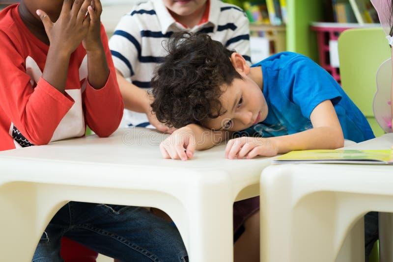 Niño del muchacho de Caucasion con la emoción de la tristeza que se sienta en sala de clase en k imagenes de archivo