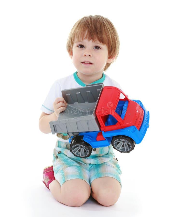 Niño del muchacho del niño que juega con el coche del juguete fotografía de archivo libre de regalías