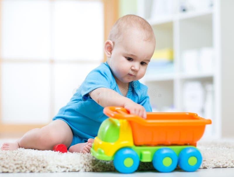 Niño del muchacho del niño que juega con el coche del juguete en cuarto de niños fotos de archivo