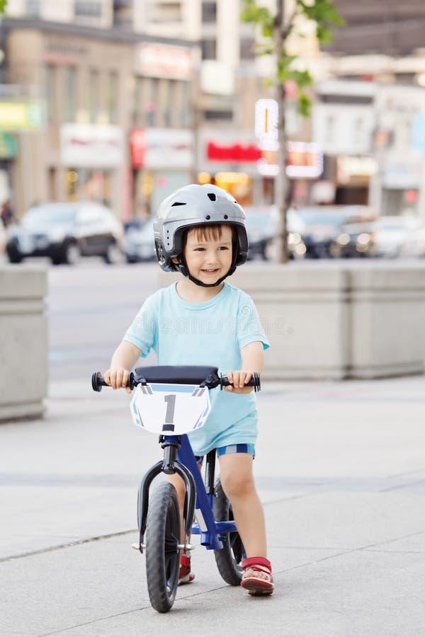 Niño del muchacho que monta una bicicleta de la bici de la balanza en casco en el camino fotos de archivo libres de regalías