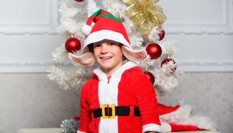Niño del muchacho vestido como los oídos artificiales blancos de la criatura mágica linda del duende y sombrero rojo cerca del ár imagen de archivo libre de regalías