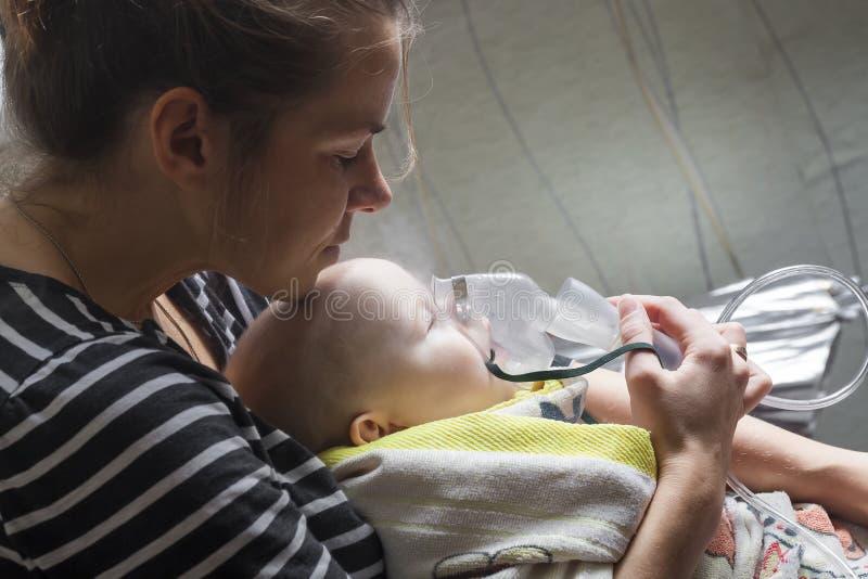 Niño del niño de la inhalación de la mamá bajo un año foto de archivo libre de regalías